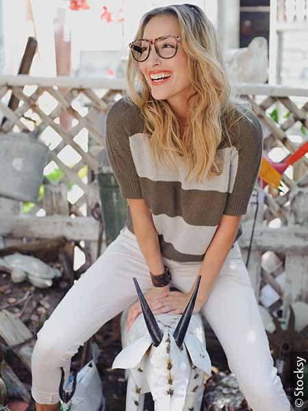 Femme blonde avec des lunettes en train de rire aux éclats