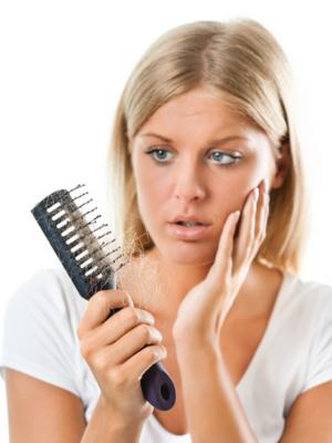 Woman shocked at her hairbrush full of hair