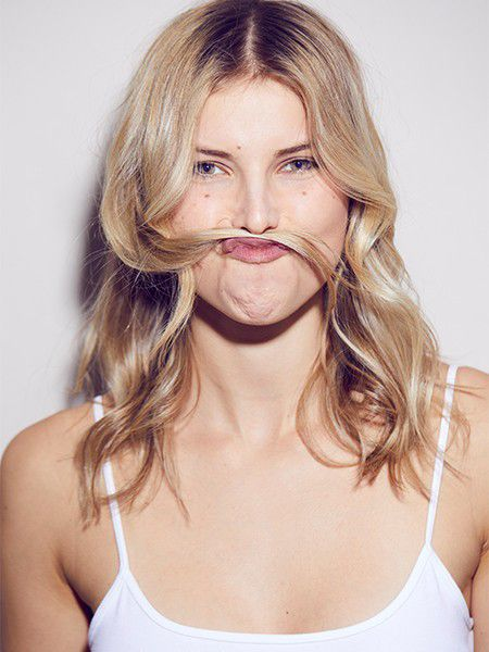 Blonde woman with hair between her top lip and nose