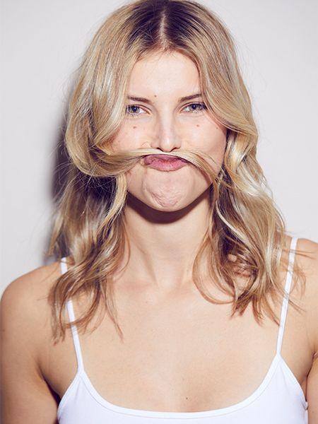 Vorderansicht einer blonden Frau in weißem Spaghetti-Top, die eine lange Haarsträhne zwischen Mund und Nase klemmt