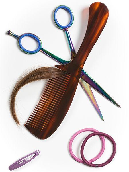 Schere, Kamm, Haarsträhne, Zopfgummis und Haarspange liegen auf einem weißen Tisch