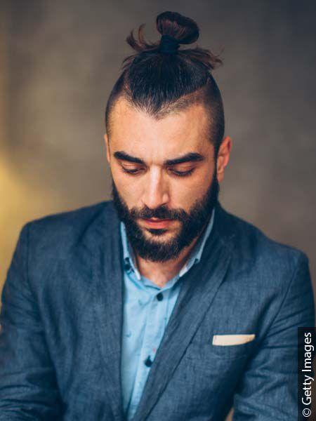 Homme élégant avec un undercut et des cheveux longs attachés en chignon