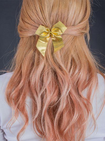 Blonde Frau trägt ihre Haare nach hinten gebunden, die mit einer goldenen Schleife verziert sind