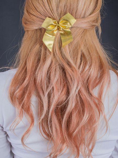 Rückansicht von einer jungen Frau mit pinkfarbenem, welligem Haar mit gelber Schleife