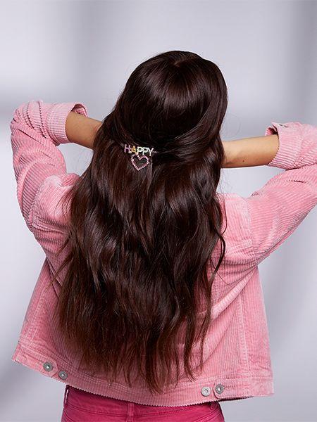 dunkelhaarige Frau mit romantischer Frisur und Happy-Haarnadel im Haar