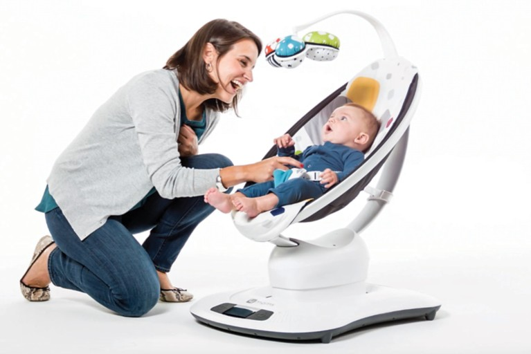 Mother engaging with her baby in a rocker