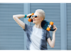 Woman with short white hair holding a skateboard