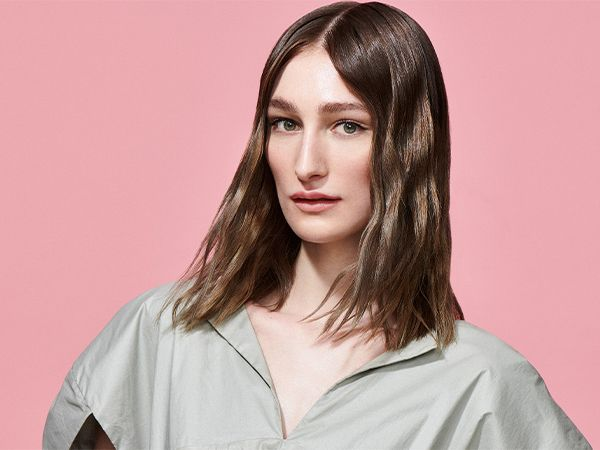 Woman with wavy hair and gray shirt with pink background