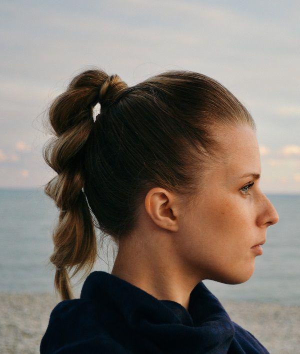 Femme de profil à la plage avec une queue-de-cheval tressée