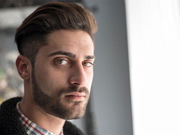 Uomo con capelli medio lunghi tirati indietro, barba e baffi corti