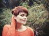 Rothaarige Frau mit kurzen Haaren und orangefarbenem Pullover