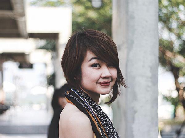 Braunhaarige Frau mit asymmetrischem Pixie-Cut lächelt den Betrachter an