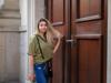 Junge Frau mit blonden, leicht zerzausten Haaren steht vor einer Tür