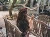 Seitenansicht einer Frau mit braunen gewellten Haaren und Flechtfrisur, die auf einer Bank sitzt und Seifenblasen pustet