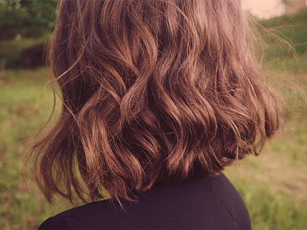 Seitenansicht von einer Frau mit kurzen, welligen Haaren