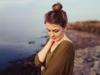 Frontansicht einer brünetten Frau mit Messy Bun, die am Seeufer steht