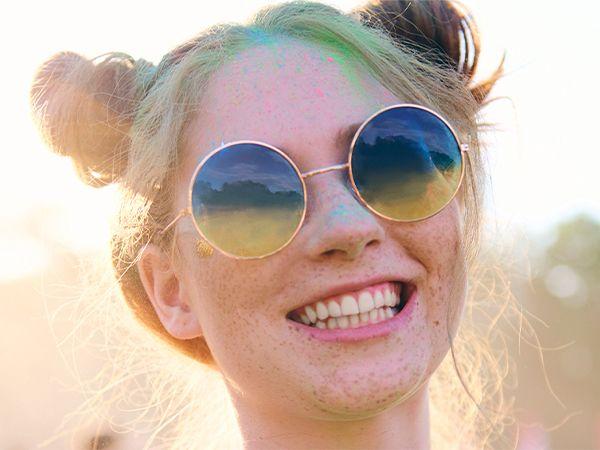 Lachendes blondes Mädchen mit Sonnenbrille und Double Buns