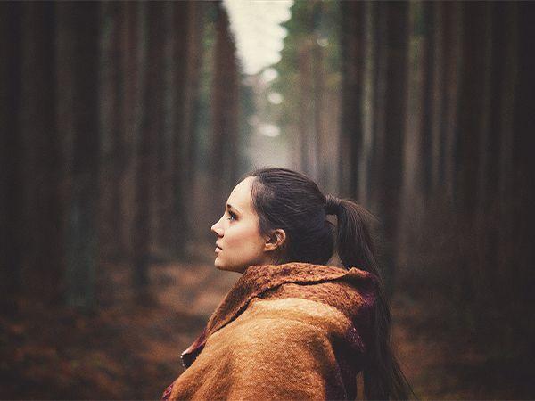 Profil einer dunkelhaarigen Frau im Wald, die einen Ponytail im Wickel-Look trägt