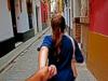 Rückansicht einer brünetten Frau mit Pferdeschwanz, die ihren Partner an der Hand hält und mit ihm durch eine Gasse läuft