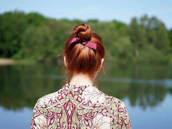 Rückansicht einer rothaarigen jungen Frau mit Top-Knot und rosa Schleifchen vor einem See