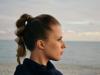 Seitenansicht einer blonden Frau mit geflochtenem Ponytail, die am Wasser steht