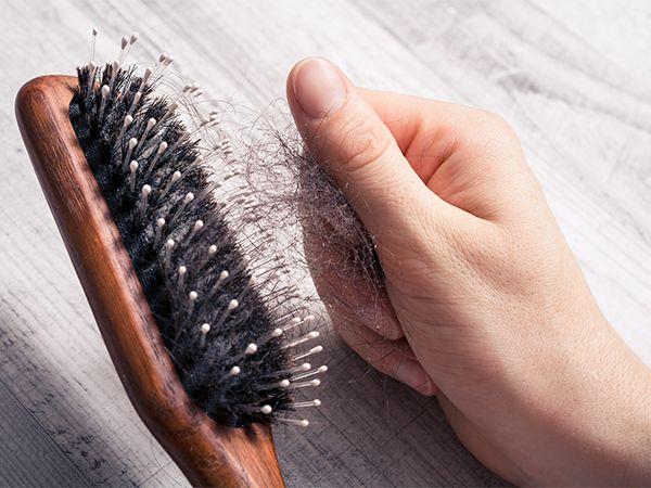 Frau entfernt Haare aus Bürste