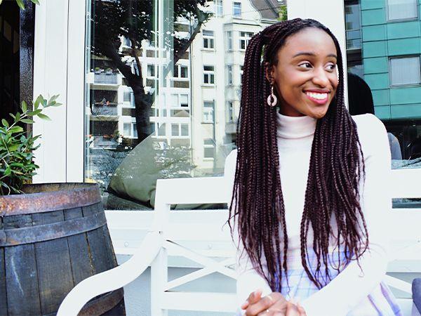 Junge, lächelnde Frau mit langen Rastabraids und weißem Pullover