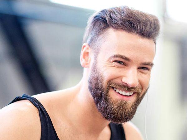 Blonder Mann mit Vollbart in schwarzem Muskelshirt lächelt
