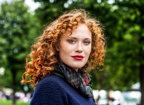 Donna dai capelli rossi ricci lunghi fino alle spalle che sorride