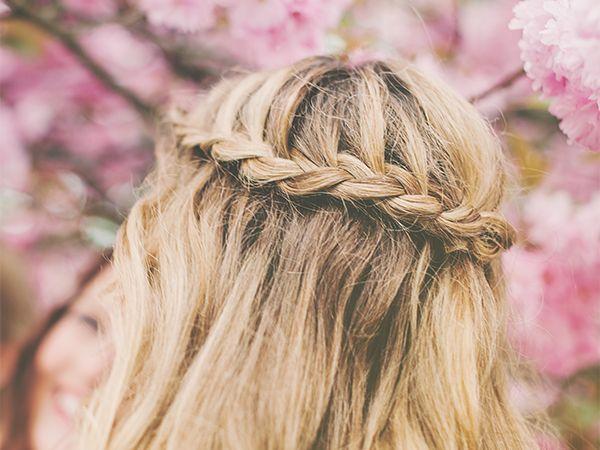 Detailshot auf eine um den Kopf gewickelte Flechtfrisur einer Frau mit blonden Haaren
