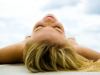 Blonde woman with eyes closed lies on her back on a beach