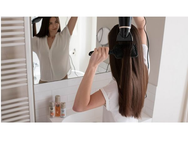 Woman styling her hair in front of a mirror
