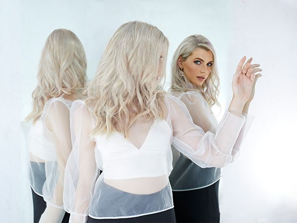 Woman with platinum blonde hair wearing a white transparent blouse in front of two mirrors.