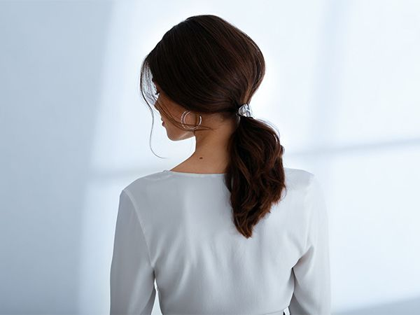 Woman with dark, backcombed hair wearing a ponytail in a clip.