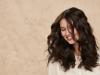 Frau mit vollem, dunkelbraunen Haar lächelt.