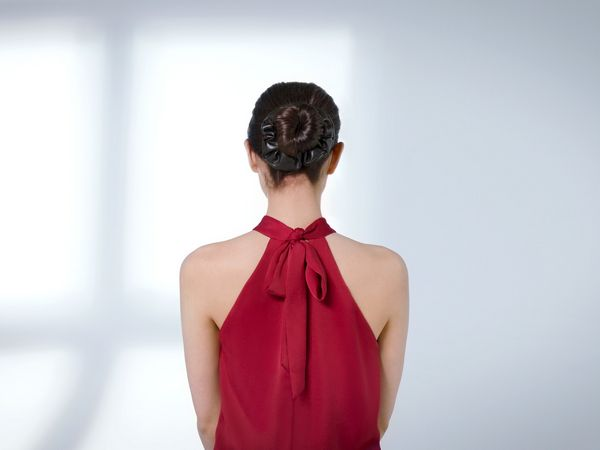 Dark-haired woman wearing a scrunchy around her bun.