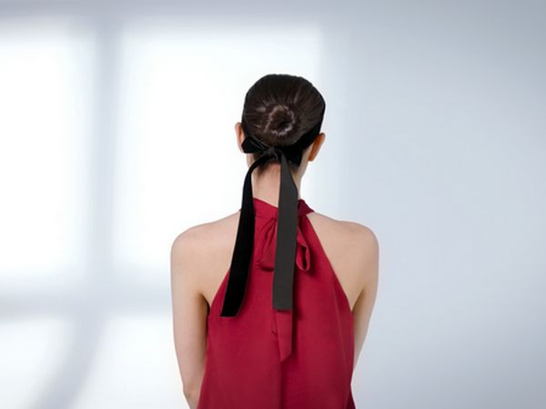 Dark-haired woman wearing a ribbon around her bun.