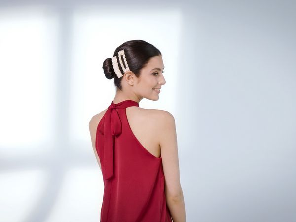 Dark-haired woman wearing clips in her bun hairstyle.