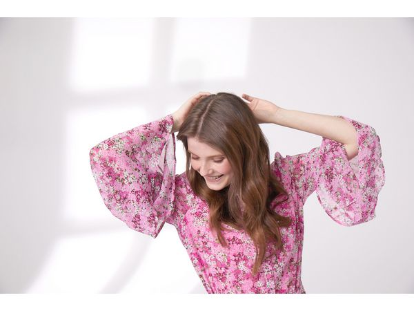 Woman smiling while touching her hair, wearing a floral dress