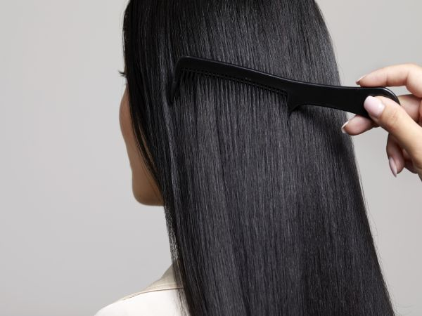 A comb running through long black hair.