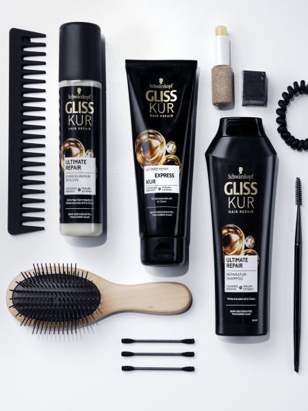 The Gliss Ultimate Repair range surrounded by a brush, comb, hair tie and other hair accessories.