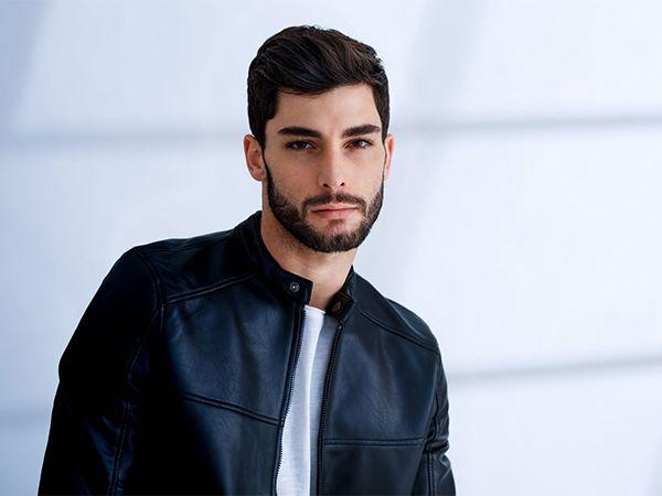 Moški s temnimi lasmi in brado z globokim stranskim delom.