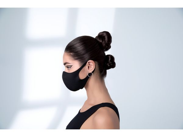 Profile of woman with double buns and wearing a face mask