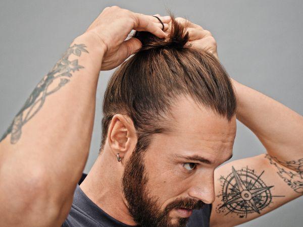 Man securing his man bun with a hair tie.