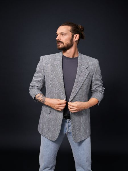 Man looking smart in a suit jacket and jeans, hair styled into a man bun.