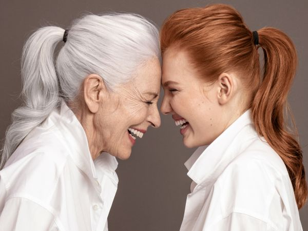 An older and a younger woman laughing together