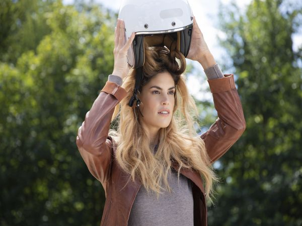 Woman taking off a motorcycle helmet, leaving her hair frizzy