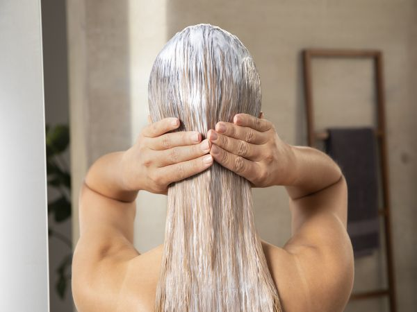 Woman massaging the Gliss Split Hair Miracle Sealing 2-in-1 Treatment Mask into her hair