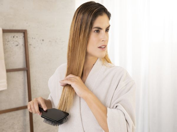 Woman brushing her hair from the bottom