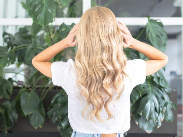 Žena dodiruje rukama dugu plavu kosu okrenuta leđima